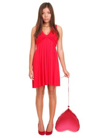 femme triste: Triste woman in love ? dr�le. Valentin femme holding malheureux coeur rouge ballon belle jeune femme en robe rouge. Mod�le f�minin asiatique  caucasien isol� sur fond blanc en pleine longueur. Concept de love de c?ur bris�.