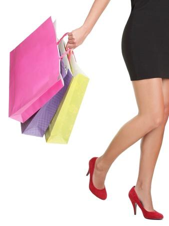 tacones rojos: Compras sobre fondo blanco. Detalle de mujer sosteniendo compras bolsas vistiendo tacones rojos.