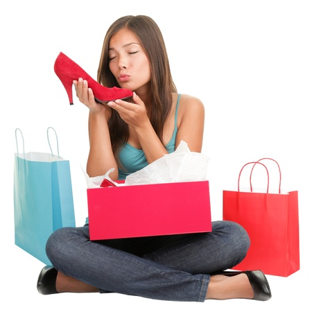 shoes fashion: Shopping woman loves shoes. Funny cute image of young woman kissing high heels shoes after shopping. Asian Caucasian woman sitting isolated on white background. Stock Photo