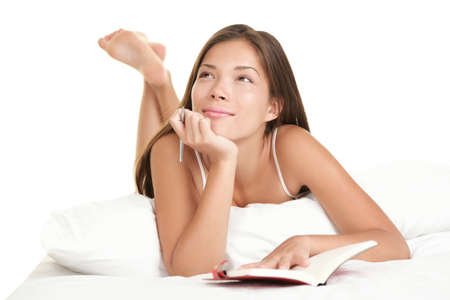 Girl writing diary or studying in bed thinking. Young Asian Caucasian model in her 20s isolated on white background.