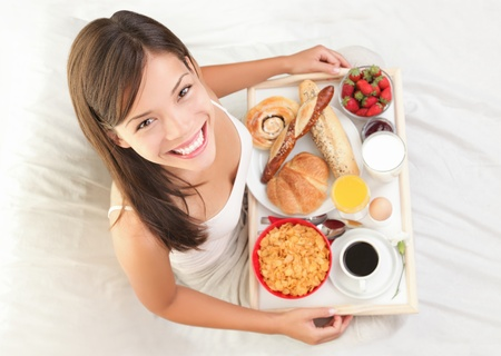 Woman having breakfast in bed. Big continental breakfast. Asian caucasian woman smiling looking at camera.