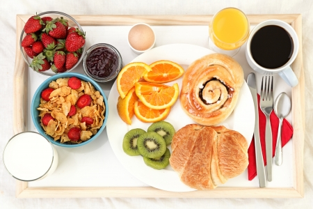 Breakfast tray in bed with coffee, bread, cereals, fruit etc. photo