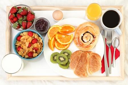 Plateau de petit déjeuner au lit avec café, pain, céréales, fruits, etc..