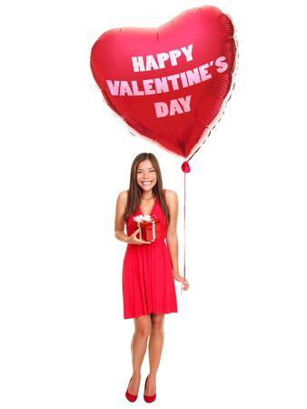 Valentines day woman holding gift and red heart balloon saying ?happy Valentines day?. Cute beautiful young woman smiling in red dress. Asian  Caucasian female model isolated on white background in full length. Stock Photo