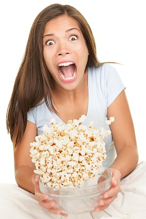 snack: Woman scared funny watching scary movie. Beautiful girl watching movie in bed on white background