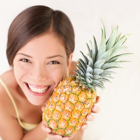 Pineapple fruit woman smiling healthy and joyful. Mixed-race Asian  Caucasian model on white background