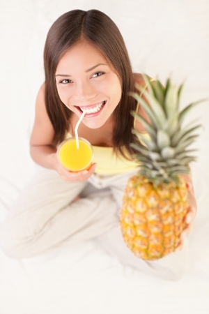 pineapple  glass: Woman drinking pineapple fruit juice smiling showing pineapples. Beautiful fresh Asian  Caucasian woman sitting in bed.