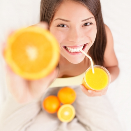 Woman drinking orange juice smiling showing oranges. Young beautiful mixed-race Asian / Caucasian model. Banque d'images
