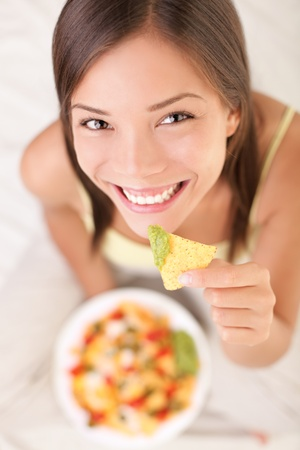 snacking: Nachos eating woman smiling looking at camera. Beautiful cute girl enjoying snacks in bed - white background.