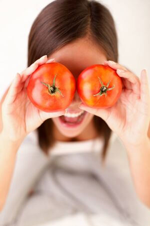 Tomato. Woman showing tomatoes. Cute funny image of girl holding tomatoes in front of her eyes.