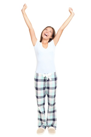 pijama: Ma�ana de mujer que se extiende en pijama sonriendo aislado sobre fondo blanco en toda la longitud. Raza mixta asi�tica  cauc�sica modelo femenino.