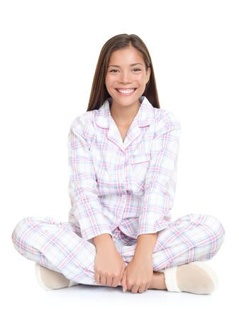 Young woman lying down cute in pajamas and slippers. Isolated on white background.