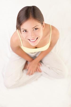 top angle view: Mujer joven sonriente - comienzo �ngulo de vista de la joven y bella mujer sentada parezca buscar en la c�mara. G