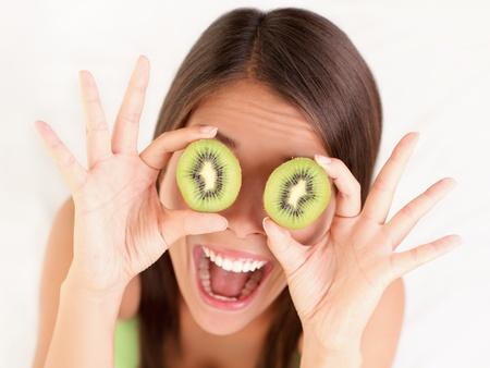 oči: Kiwi. Healthy fruit funny woman holding kiwi fruit for her eyes.