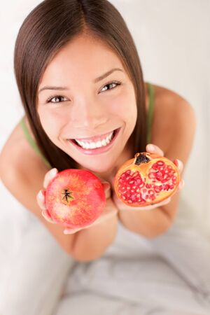 Pomegranate fruit. Woman showing pomegranate smiling. photo