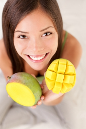 snack: Mango fruit. Woman showing a mango fruits, cut and sliced.