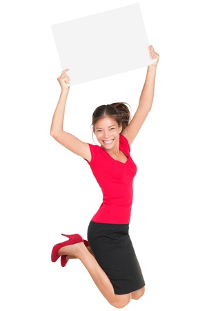 Sign woman jumping excited and happy showing blank empty sign card with copy space for your text. Beautiful smiling young female model isolated in full length on white background.