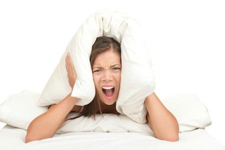 ruido: Mujer de cama cubriendo orejas con la almohada de ruido. Imagen divertida aislada sobre fondo blanco.