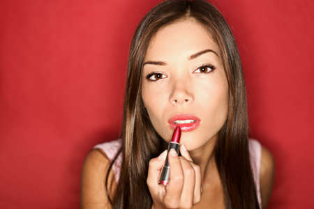 Woman putting red lipstick looking in mirror. Makeup at night getting ready before going to party. photo