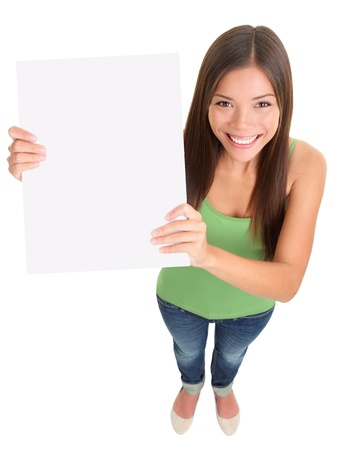 placard: Sign woman smiling standing isolated. Top view of multi ethnic girl showing blank empty sign board with copy space for text message etc. Pretty female mixed-race asian Caucasian female model cut out in full length on white background.