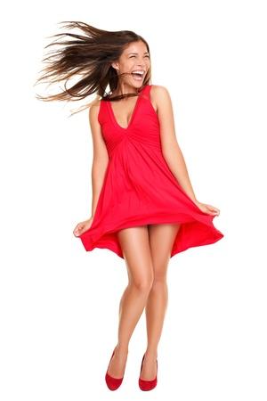 viento: Sexy mujer loca excitada y gritando con viento en el pelo. Hermosa modelo asi�tico feliz permanente l�dica en vestido rojo aislada sobre fondo blanco.