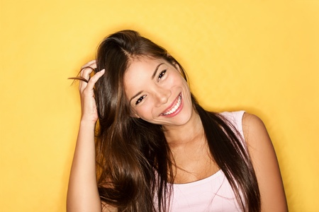 Smiling casual woman playful on yellow background. Beautiful multiracial Asian  Caucasian female model joyful. photo