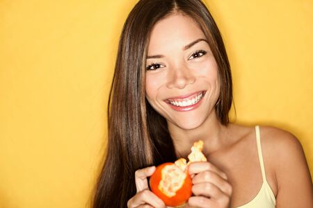 Woman eating orange smiling on yellow background. Candid natural beauty eating healthy. Stock Photo