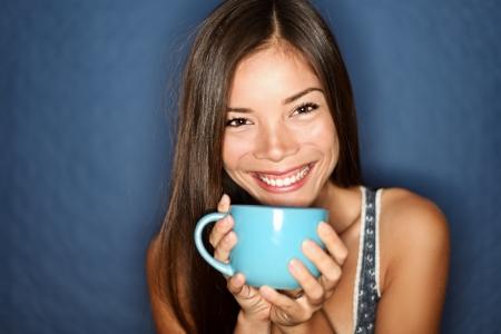 Woman smiling drinking tea on blue background. Young beautiful multiracial Asian / Caucasian female model joyful.