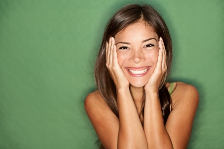 Surprised excited woman on green background. Cheerful multiracial Asian  Caucasian female model joyful.