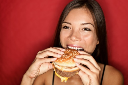 Burger woman smiling eating junk food burger happy. Pretty mixed race caucasian  asian girl on red background.