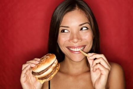 comida chatarra: Mujer comiendo hamburguesa y papas fritas sonriendo. Bella mestiza cauc�sica femenina modelo asi�tico sobre fondo rojo. Foto de archivo
