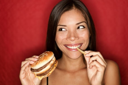 eating out: Woman eating burger and fries smiling. Beautiful mixed race asian caucasian female model on red background. Stock Photo