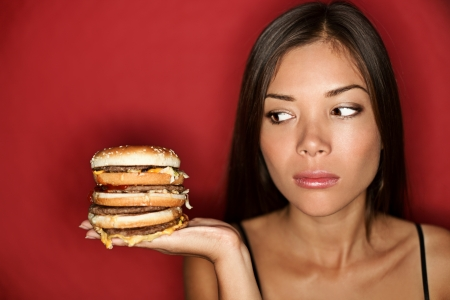 Unhealthy eating - junk food concept. Woman looking at big oversized burger thinking. Pretty Caucasian Asian model over red background. Stock Photo