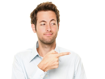 sneaky: Young man pointing a bit sneaky looking at copy space. Handsome young Caucasian businessman isolated on white background.