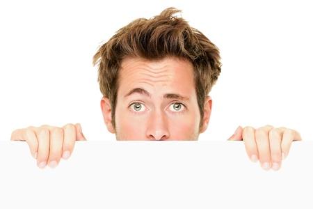 Mann peaking Ergebnis leer leere weiße Billboard Zeichen überrascht. Nahaufnahme des jungen Mannes peeping über weiß Banner Rand. Isolated on white Background. photo