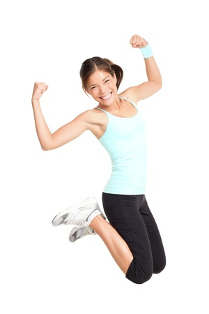 Fitness woman jumping excited isolated on white background. Full body image of beautiful multiracial Asian Caucasian female model in jump flexing and showing muscles. photo