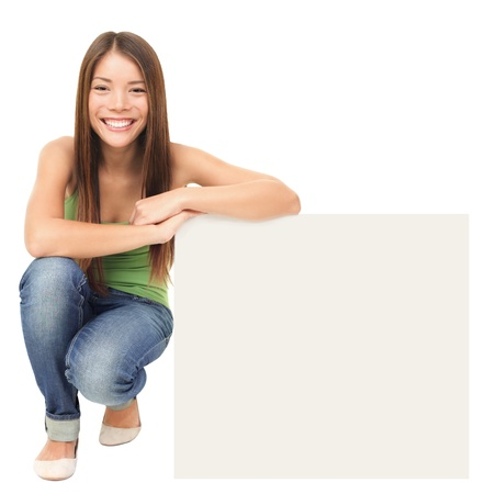 holding a sign: Woman sitting showing billboard sign. Cute casual young beautiful woman holding blank white commercial sign isolated on white background. Lovely fresh asian caucasian female model in full length.