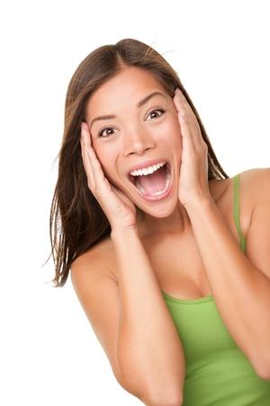 donna entusiasta: Sorpresa eccitata donna urlando stupito nella gioia. Bella donna giovane isolata su sfondo bianco in canottiera verde casual. Asian caucasica multirazziale modello femminile nel suo 20s.