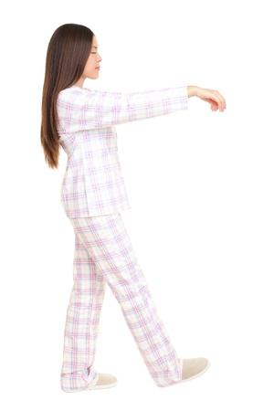 pajamas: Mujer de sonambulismo aislada sobre fondo blanco. Vista de perfil de joven por su capacidad en pijama con los brazos alzados. Imagen de longitud completa