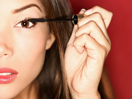 Woman putting mascara makeup. Closeup of gorgeous multi-ethnic Chinese Asian / white Caucasian female model getting ready for a night out.