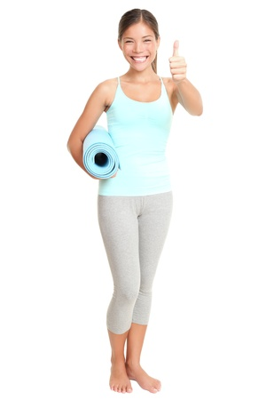 Fitness woman giving success thumbs up sign standing holding exercise yoga mat. Young sporty fit mixed race Asian  Caucasian female model isolated on white background in full body.