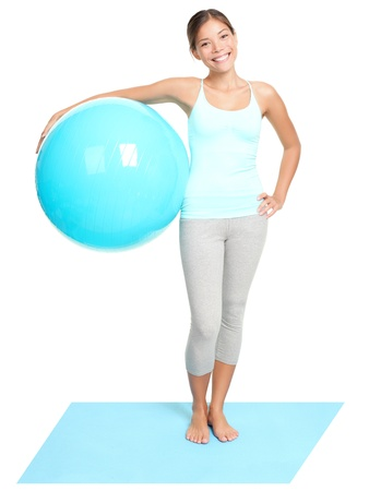 Fitness woman holding exercise pilates ball. Young sporty fit mixed race Asian / Caucasian female model standing isolated on white background in full length Stock Photo - 9152614