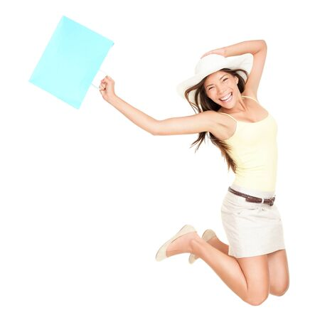 shopper: Summer shopping woman jumping of joy excited over the summer sales. Beautiful mixed race woman isolated on white background. Asian Chinese and Caucasian ethnicity.
