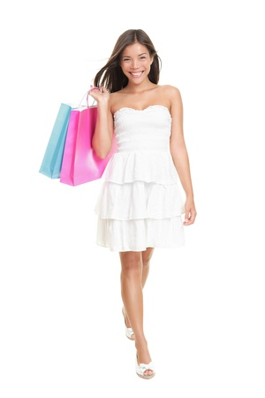 Shopping woman in summer dress holding shopping bags walking elegant in full length. Gorgeous and fresh young mixed race ethnic female model isolated on white background. Asian Chinese and Caucasian ethnicity. Banco de Imagens