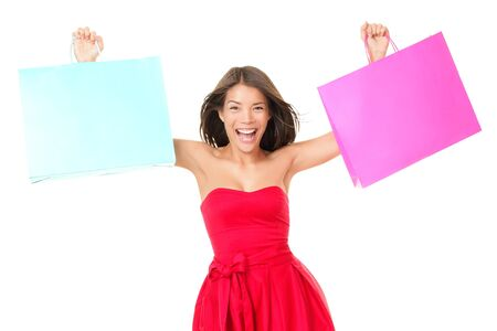 Shopping woman in red dress showing shopping bags with copy space for sign or your text. Beautiful excited fresh young mixed race ethnic female model isolated on white background. Asian Chinese and Caucasian ethnicity. Stock Photo