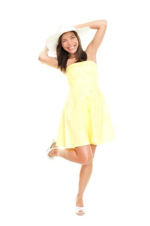 遊び心と陽気な夏のドレスの女性。白い背景と完全な長さで分離されました。美しい新鮮な若い混血民族女性モデルでは、黄色のドレスと夏用帽子