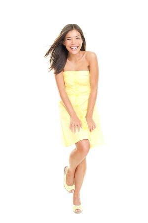 Vrouw in gele jurk glimlachend gelukkig, vrolijke en speelse. Geïsoleerd op een witte achtergrond in volle lengte. Prachtige verse jonge gemengd ras Aziatische Kaukasische vrouwelijke model in leuke zomerjurk.