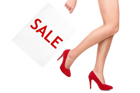 rebate: Shopping bag woman - sale sign. Closeup of woman legs and shopping bags saying sale. Isolated on white background.