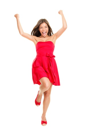 Woman happy cheering in summer dress - playful and cheerful. Isolated on white background in full length. Beautiful fresh young mixed race ethnic female model in red dress-