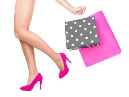 tacones rojos: Bolsa de compras mujer - concepto de comprador. Detalle de las piernas de la mujer y bolsas de compras-aislado sobre fondo blanco. Foto de archivo